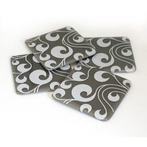Swirls in white, on grey coaster set