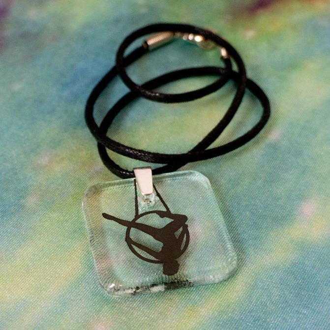 "Aerial Trapeze Pendant, fused and hand-drilled, with a sterling silver clasp and 16"" cotton cord necklace"